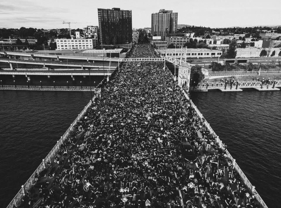 Portland's Burnside Bridge, thousands of protesters kneel to protest deadly anti-Black racism.